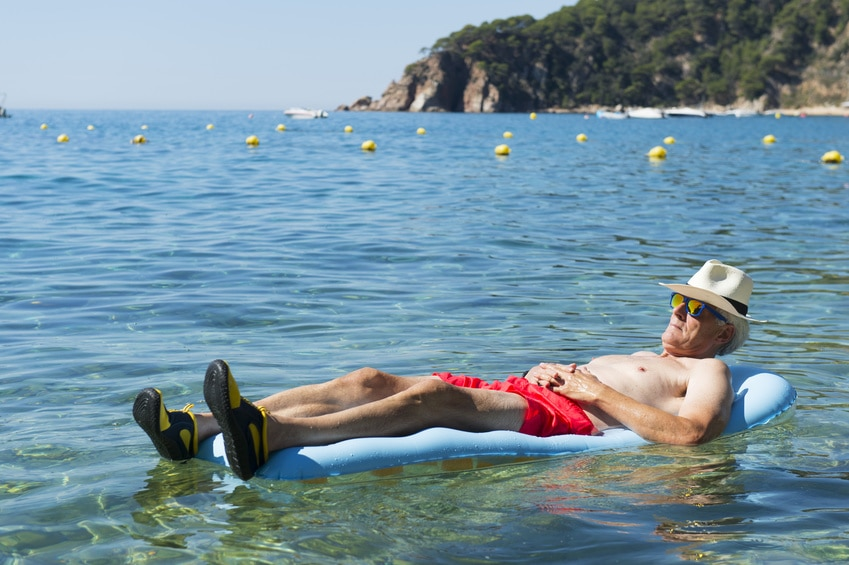 Retired man laying on inflatable bed floating in the sea